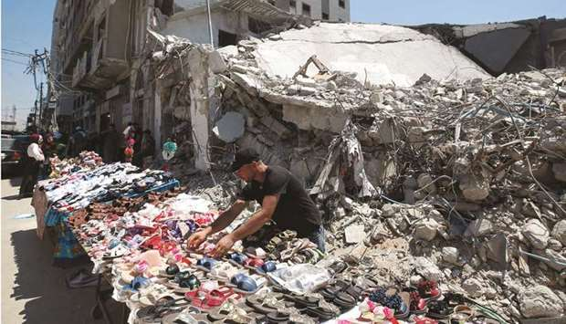A Palestinian sells shoes on a stall near the rubble of his old shoe store that has been destroyed i