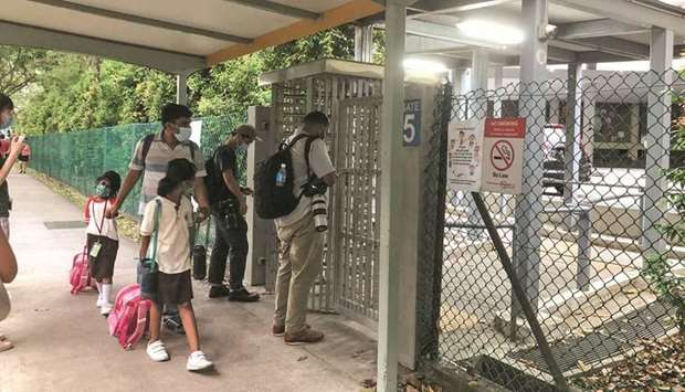 People pick up students leaving River Valley High School in Singapore yesterday.