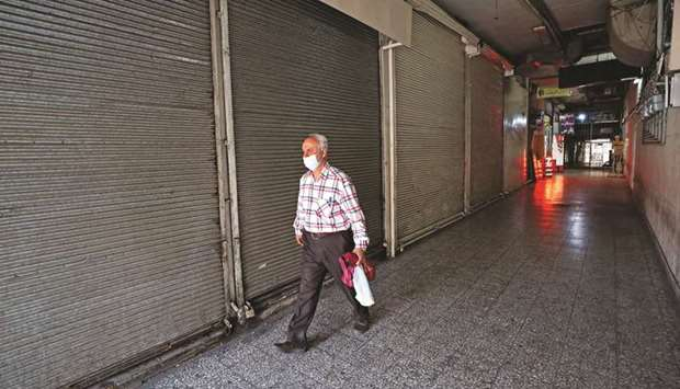 An Iranian man wearing a protective face mask walks past shuttered stores at a commercial centre i