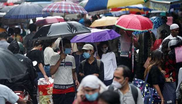 People walk through a crowded market on a rainy day amidst the spread of the coronavirus disease in