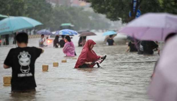 Residents wade through floodwaters on a flooded road amid heavy rainfall in Zhengzhou, Henan provinc