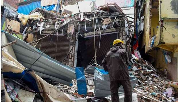 A civil authority worker removes debris from a collapsed building in Mumbai.
