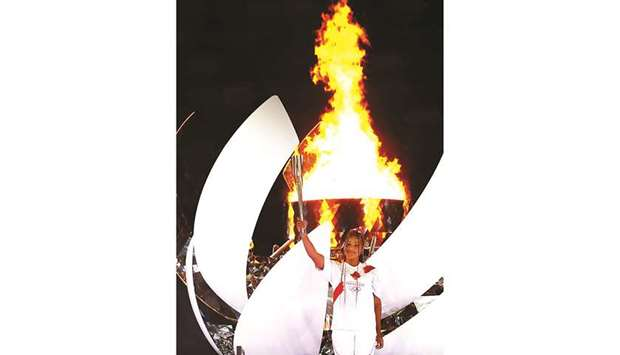 Japan's tennis star Naomi Osaka holds the Olympic torch after lighting the Olympic cauldron at the o