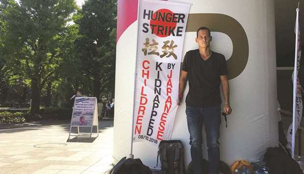 French father-of-two Vincent Fichot stands next to a banner where he has been on a hunger strike sin