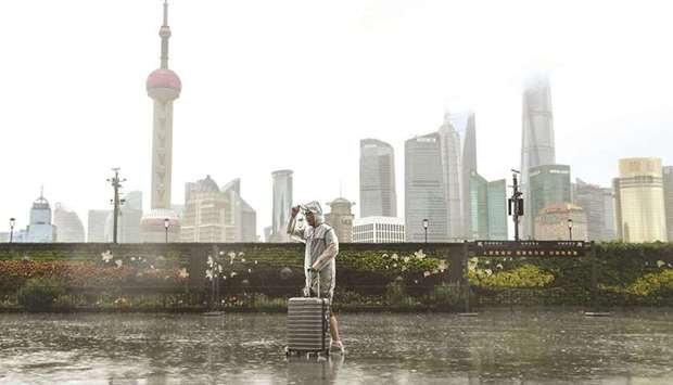 A man with luggage walks in the rain on The Bund as Typhoon In-fa approaches Shanghai, China, yester
