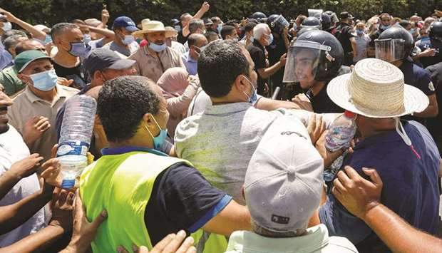 A police officer pushes back supporters of Tunisia's biggest political party, the moderate Islamist
