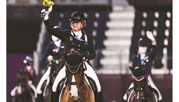 Gold medallist Isabell Werth of Germany rides on her horse together with other medallists after the