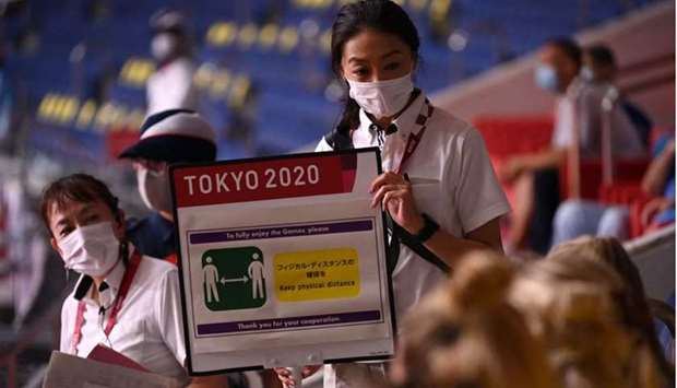 An IOC volunteer shows a sign to Sweden's delegation members reminding to respect the Covid-19 count
