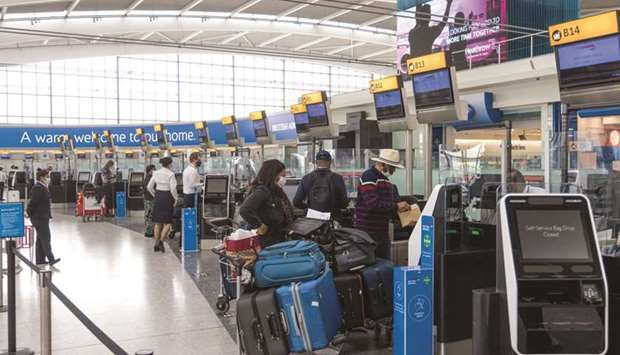 Passengers wait at check-in desks in the departures hall in Terminal 5 at London Heathrow Airport. B