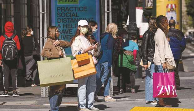 People wearing protective masks carry shopping bags while waiting to cross Geary Street in San Franc