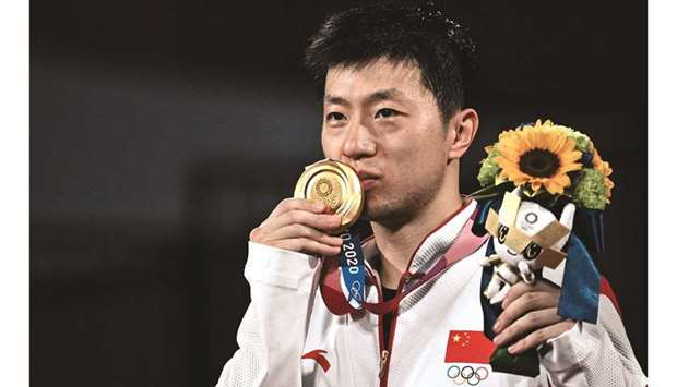 China's Ma Long kisses his medal during the men's singles table tennis medal ceremony at the Tokyo M