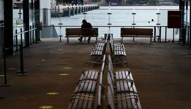 A lone man sits on a bench at the quiet Circular Quay during a lockdown to curb the spread of a coro