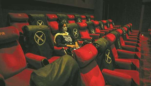 A woman watches a movie at a multiplex after cinema theatres reopened with 50% occupancy as the coro