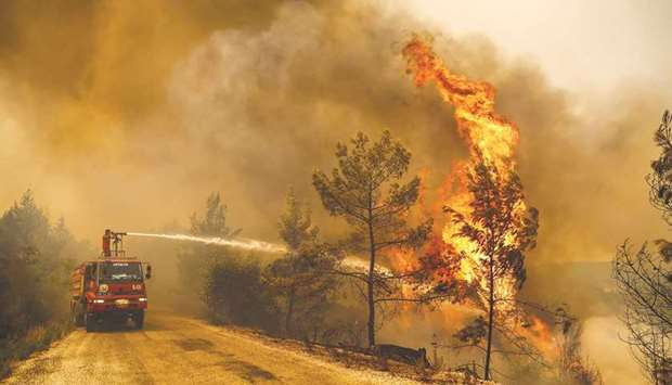 A firefighter works to extinguish a fire near the town of Manavgat, east of the resort city of Antal