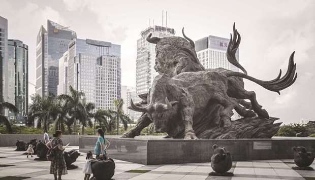 People stand in front of a sculpture of bulls at the entrance to the Shenzhen Stock Exchange buildin