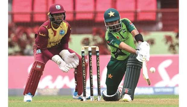 Babar Azam of Pakistan plays a shot as West Indies' Nicholas Pooran looks on during the 3rd T20I at