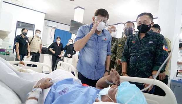 Philippine President Rodrigo Duterte salutes a wounded soldier who survived from the C-130 plane cra