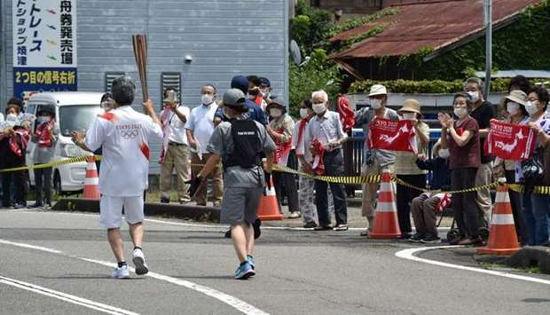 A torch bearer (L) running with the Olympic torch past spectators during the Tokyo 2020 Olympic Game