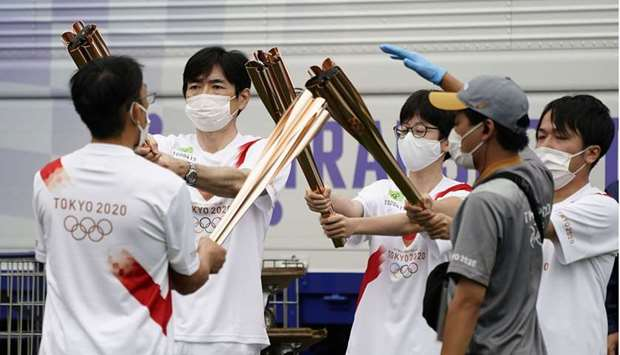 Torchbearers practice torch kiss before a lighting ceremony, after their relay on a public road was