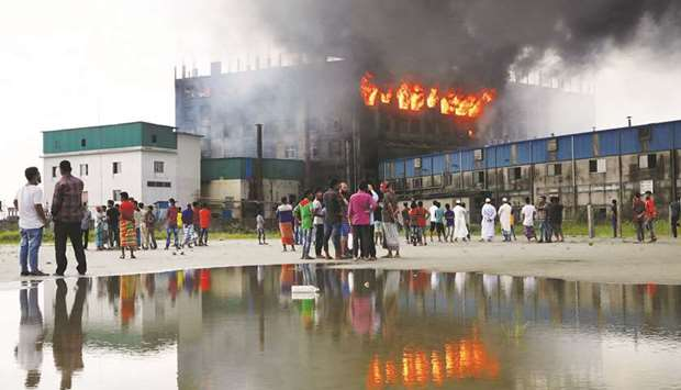 People look on as flames rise after a fire broke out at a Hashem Foods factory in Rupganj, Narayanga