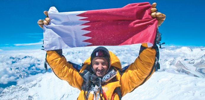 Sheikh Mohamed holds up the Qatari flag after reaching the summit of Mount Everest.