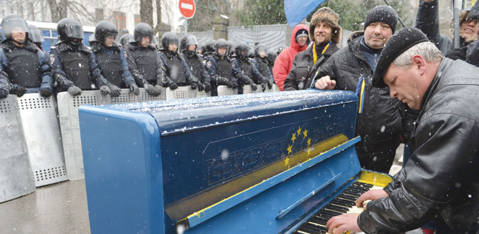 A man plays on a piano decorated with EU flag yesterday in front of riot police as protesters picket