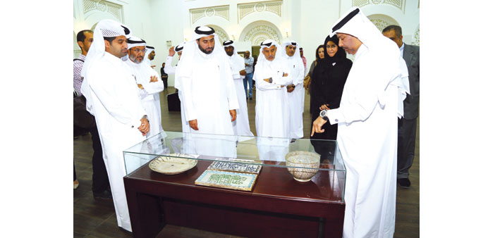 Jassim Telefat (centre), along with fellow guests, viewing artefacts at the 'Arabic Script' exhibiti