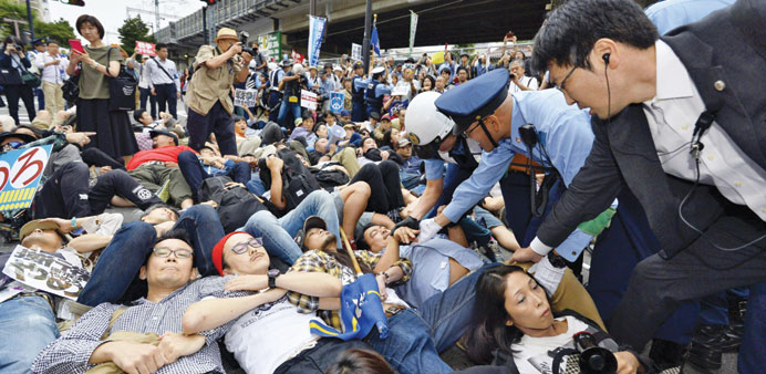 Protesters lie on the ground as they try to stop a car carrying members of the parliament's upper ho
