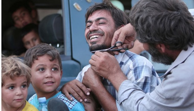 A man cuts the beard of a civilian who was evacuated with others by the Syria Democratic Forces (SDF
