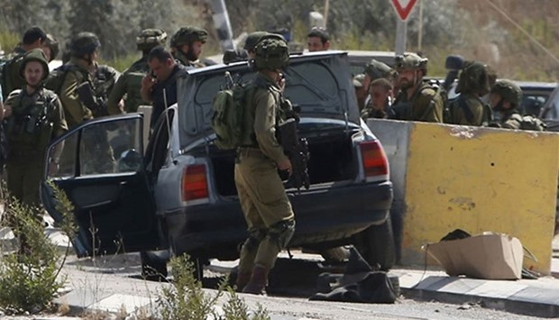 Israeli soldiers gather next to a vehicle belonging to a Palestinian man after he reportedly charged