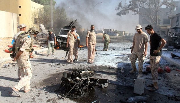 Fighters from forces loyal to Government of National Unity look at what remains of a burnt car in Si