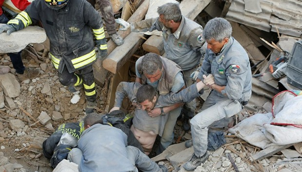 A man is rescued alive from the ruins following an earthquake in Amatrice, central Italy