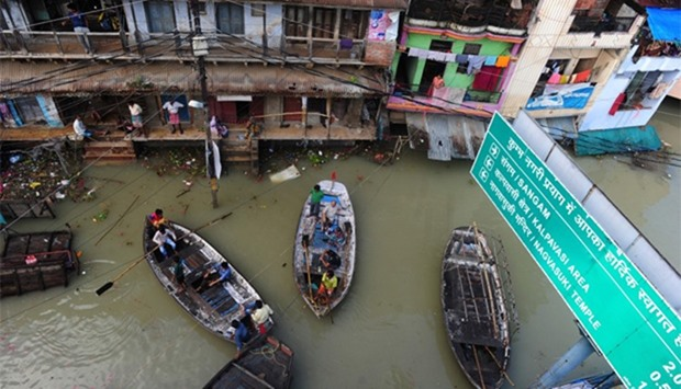 Indian flood-affected residents use boats as they attempt to shift to dry ground