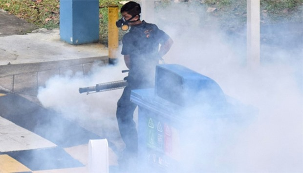 Singapore on April 5, 2016 shows a worker fumigating an area against mosquitoes