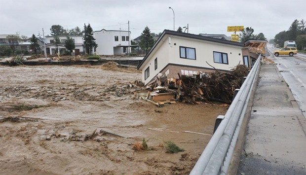 This picture shows a house swept down a river at the town of Shimizu in Hokkaido prefecture, after T