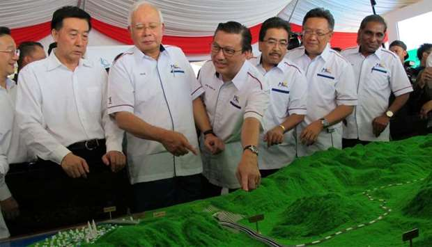 Malaysia's Prime Minister Najib Razak and Transport Minister Liow Tiong Lai look at a model of the E