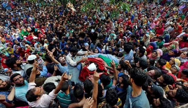 People shout slogans as they gather around the body of Shabir Ahmad Mir, a suspected militant