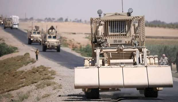 A US military demining vehicle leads a convoy on the main road in Raqqa