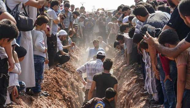 Members of the Syrian civil defence volunteers, also known as the White Helmets, bury their fellow c