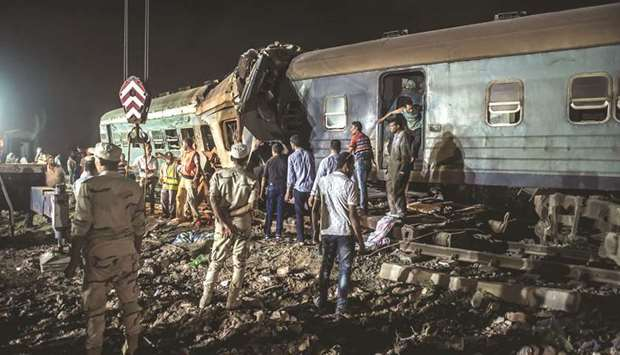 Emergency personnel and Egyptian military police search the wreckage of the train collision near Kho