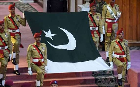 Pakistani soldiers carry the national flag during an Independence Day ceremony in Islamabad