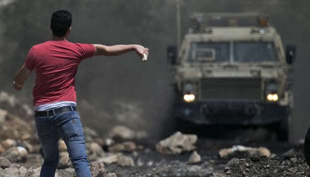 A Palestinian protester throws a rock towards Israeli security forces during clashes following a wee