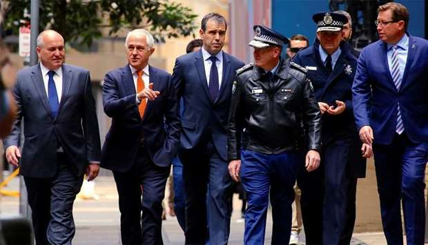 Australian Prime Minister Malcolm Turnbull walks with officials along a street