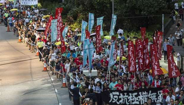 Protesters march in Hong Kong to protest the jailing of the leaders of Hong Kong's 'Umbrella Movemen