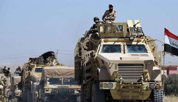 Iraqi government forces drive down a road leading to Tal Afar
