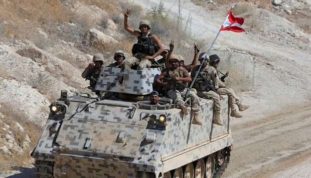 Lebanese army soldiers are seen flashing victory signs in the town of Ras Baalbek, Lebanon, yesterda