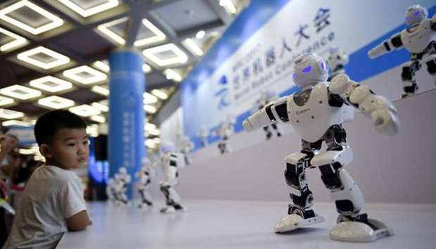 A boy watches as robots perform a dance at the 2017 World Robot Conference in Beijing