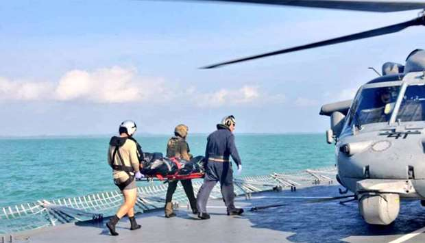 Royal Malaysian Navy personnel carry a body onto a US Navy helicopter