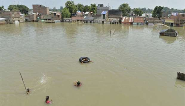 Residents swim and wade through flood waters in Malda in the Indian state of West Bengal