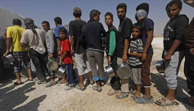 Displaced Syrians queue up to receive food at the Al-Mabrouka camp in the village of Ras al-Ain on t